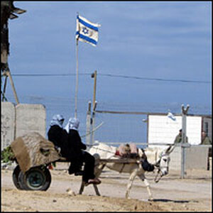 Palestinian women in a cart pass the entrance to the Jewish settlement of Shirat Hayam.
