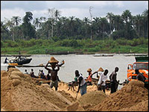 Men collect sand for the construction industry along the River Nun.