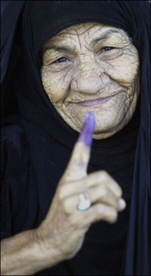 An Iraqi woman shows her inked finger after voting.