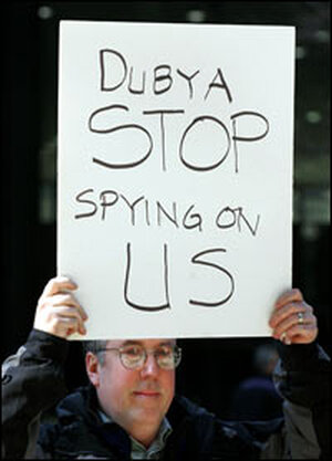 Erik Haugsnes displays a sign: 'Dubya Stop Spying on Us'