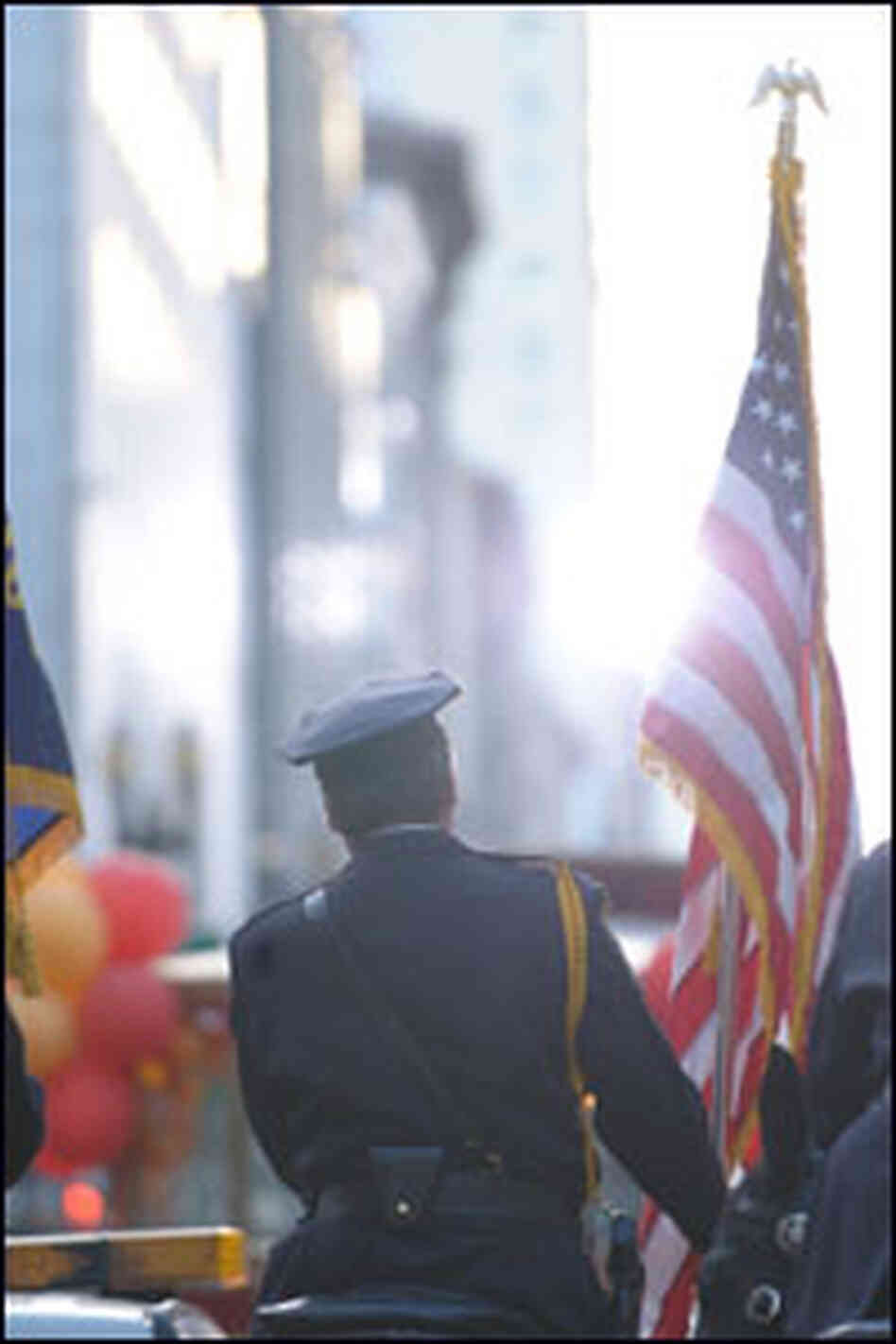A policeman holds an American flag in a parade.