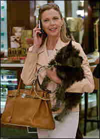 Annette Bening carries dog, talks on cell