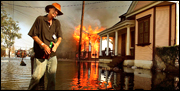 A resident walks past a burning house fire in the Seventh Ward Sept. 6, 2005 in New Orleans.