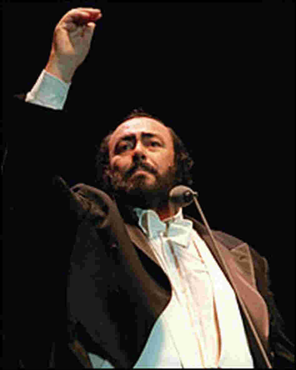 Luciano Pavarotti raises his hand to cue the audience in a sing-along encore.