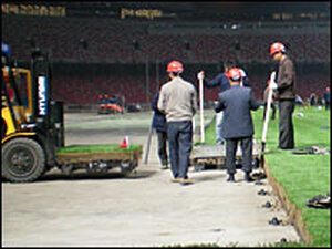 Workers install a portable turf system in May as a test move for the Olympics.
