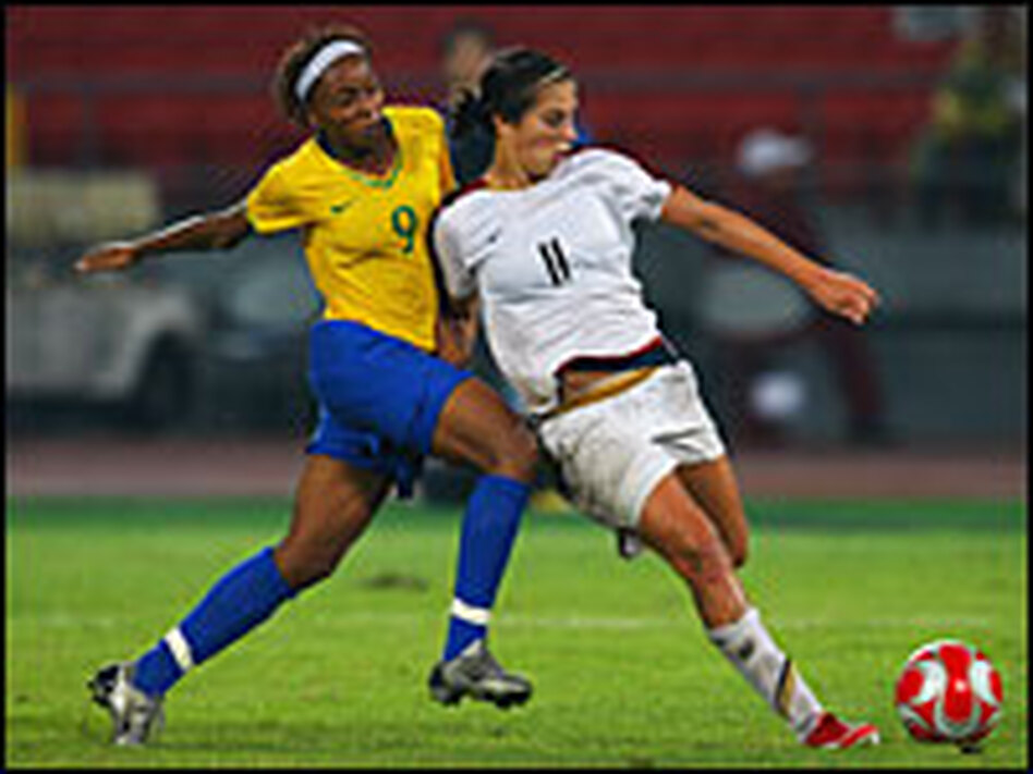 American Carli Lloyd (right) holds off the challenge from Ester of Brazil  during the women's gold medal match Thursday.