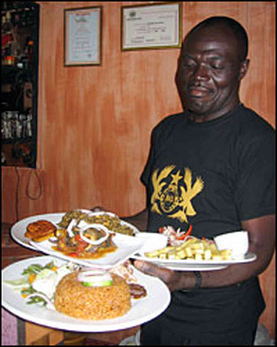 A waiter carries an array of West African dishes at Buka Restaurant, a stylish local eatery in Accra