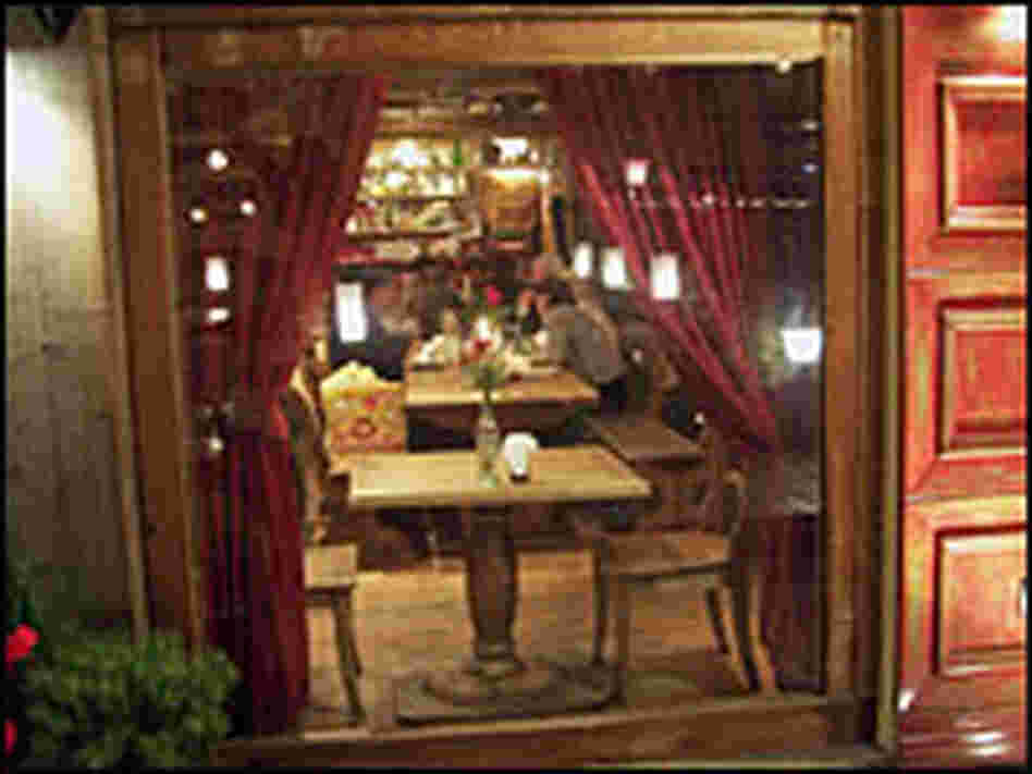 The dining room features long tables and red-cushioned booths.