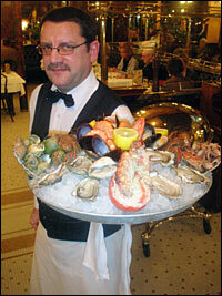 A waiter at Alsatian brasserie Bofinger carries one of the eatery's signature dishes — a platter of <em>fruits de mer</em>, or shellfish. Bofinger is the oldest brasserie, or brewing house, in Paris.