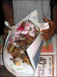After all the toppings are added, the sizzling mix is wrapped up in old newspapers.