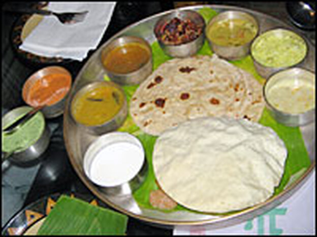 <em>Thali</em> — an array of South Indian dishes served on a banana leaf — is one of the delicious and inexpensive choices at Naivedyam in New Delhi's trendy Haus Khas village.