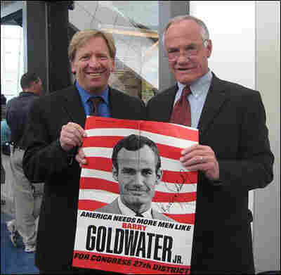 Ken Rudin and former Rep. Barry Goldwater Jr. hold up a 1969 Goldwater poster from Ken's collection.