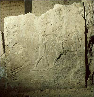 A relief sculpture portraying Assyrian soldiers marching into battle.