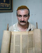 Emad Levy holds a 200-year-old Torah scroll