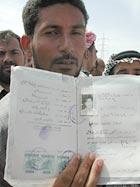 An Iraqi man holds identification papers of a missing relative as he stands patiently to hear the names of those being identified.