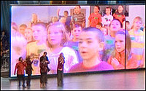 Singers are dwarfed by children on a video screen at a church service at Willow Creek.