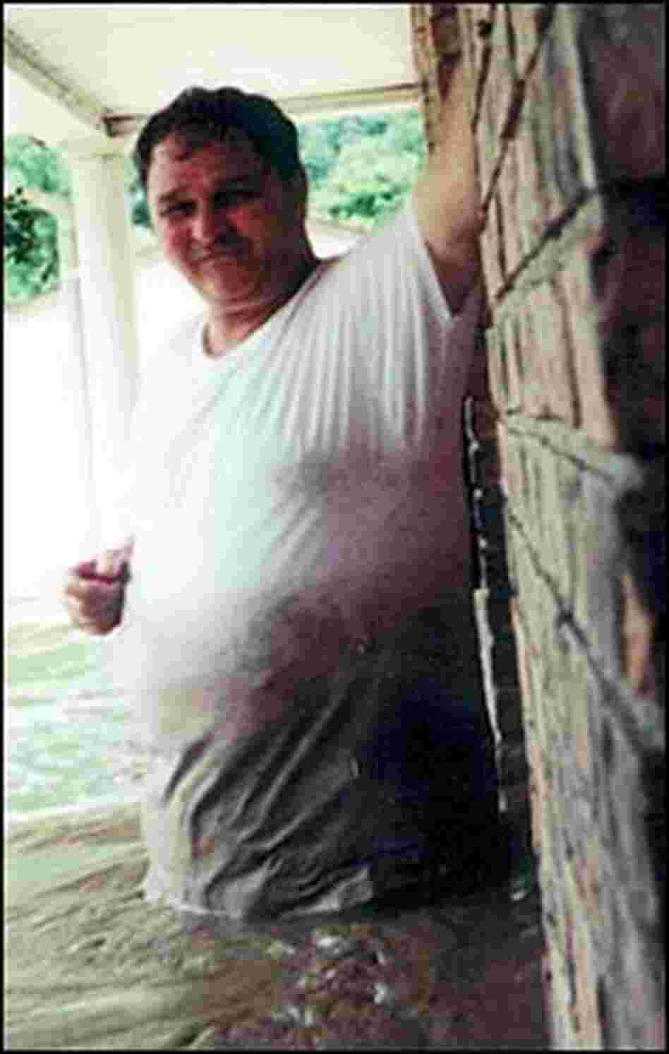 Harold Worley stands in water during the July 2001 flood in Mullens, W.Va.