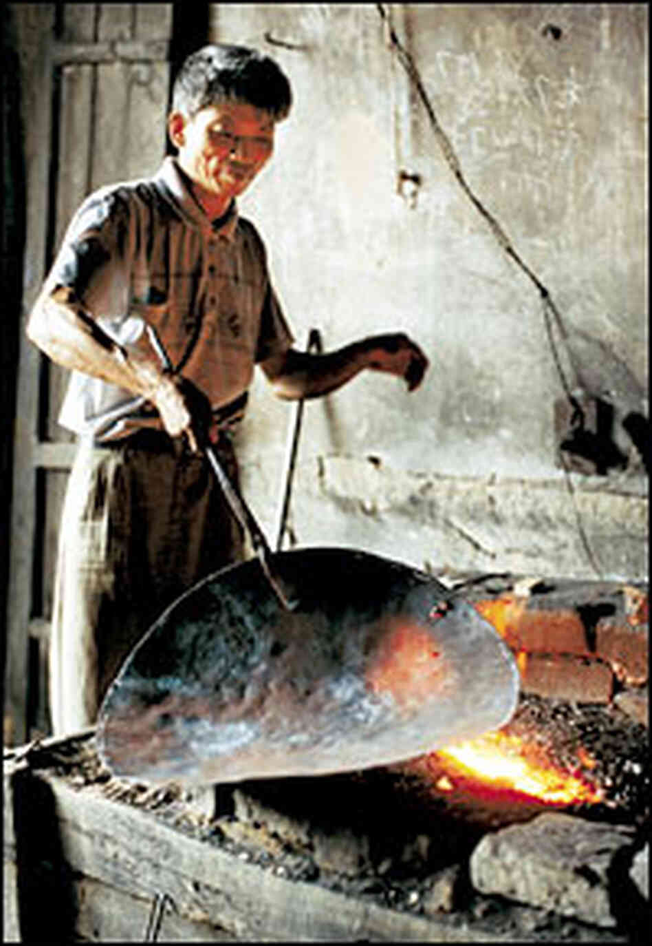 A blacksmith in Gao Tian village, in Guangxi province, makes a wok at his forge.
