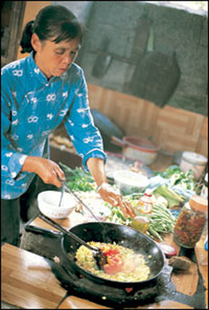 Liang Nian Xiu prepares Moon Hill Corn and Beans on a traditional hearth stove.