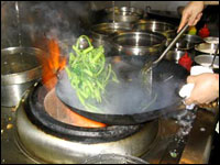 Flames roar up around a wok as it's lifted from the stove.