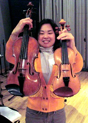 Chien Tan holds a treble violin (right) and standard violin to show the size comparison.