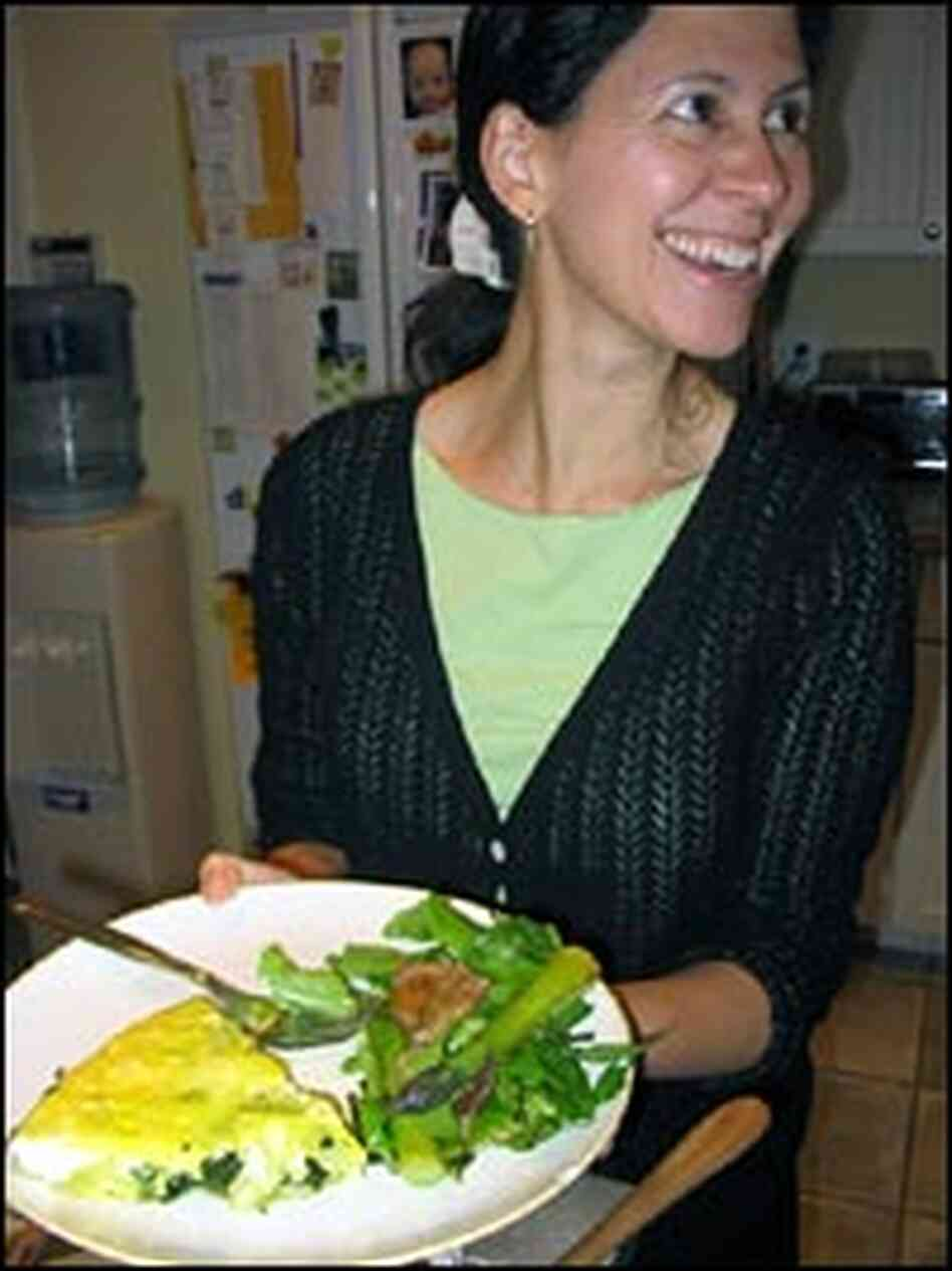 Melissa Block holds plate of frittata and a green salad topped with asparagus and grilled beef.