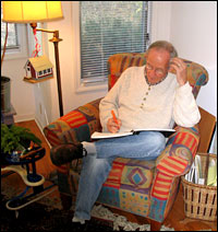 Kooser sits in his chair with a notebook in his lap.