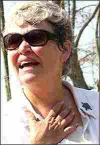Mary Anderson Pickard, wearing sunglasses, holds a hand to her throat.