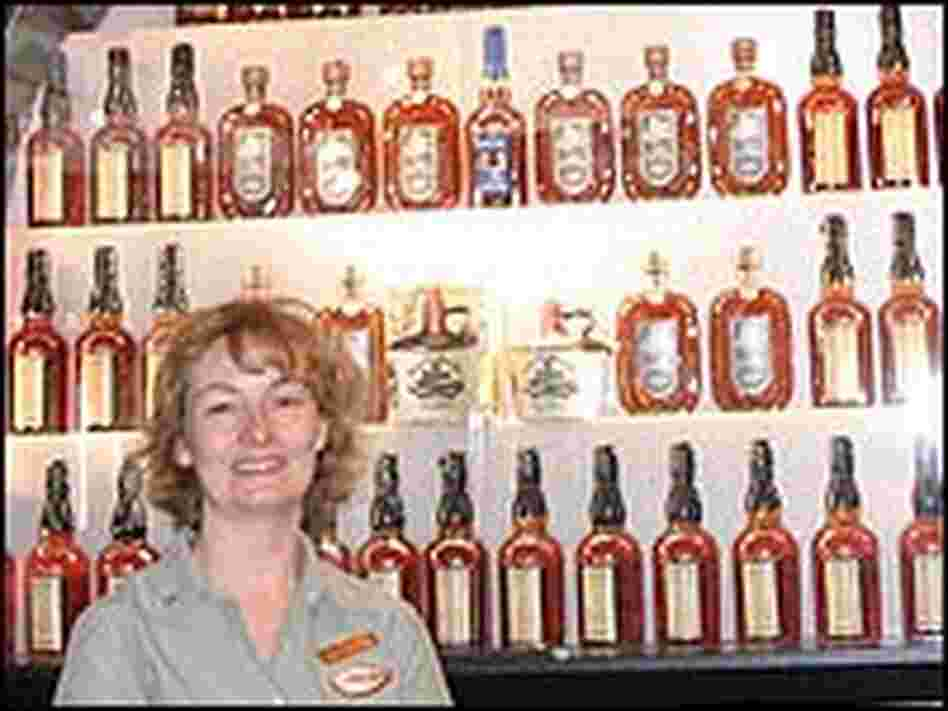 Lynn Grant stands in front of a wide variety of potent potables.