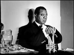 Louis Armstrong, caught in a reflective moment, his shadow against a white wall.