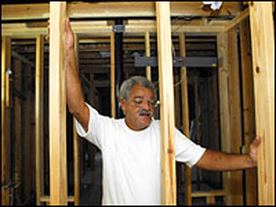 Eric Arnaud surveys rebuilding inside the portion of his home that was gutted after Katrina.