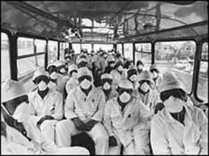 A month after the explosion, Chernobyl employees head off by bus to begin another day's work