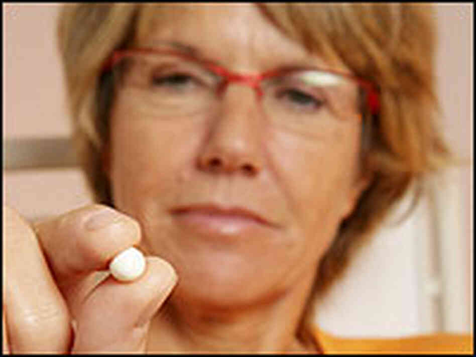A woman holding a hormone therapy pill.