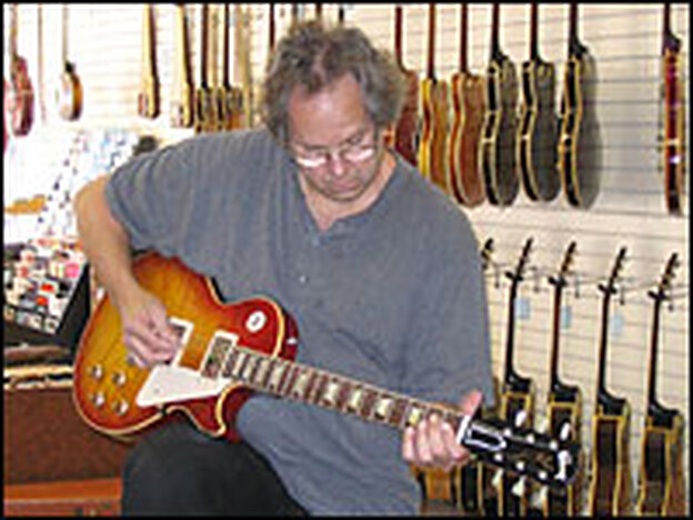 Gil Southworth strums a Gibson Les Paul Sunburst at his shop in Bethesda, Md. Christie's auction house sold a 1959 model of the guitar for $265,000 last year.