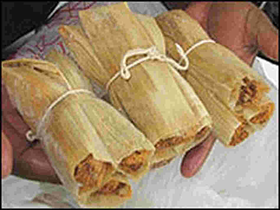 A man holds several finished bundles of tamales.
