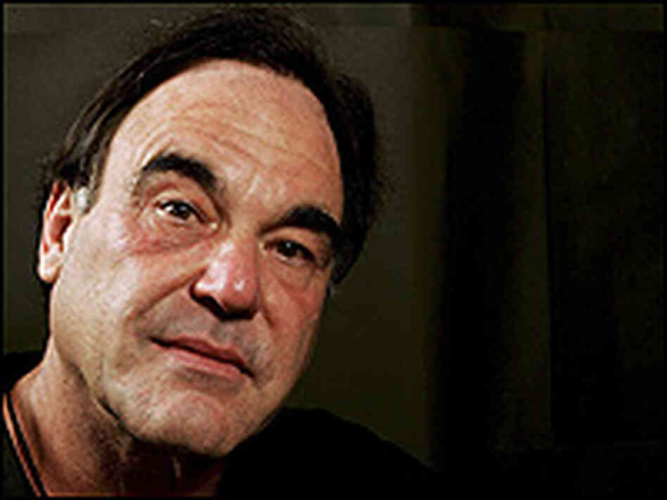 A tight shot of Oliver Stone, wearing a black polo shirt.