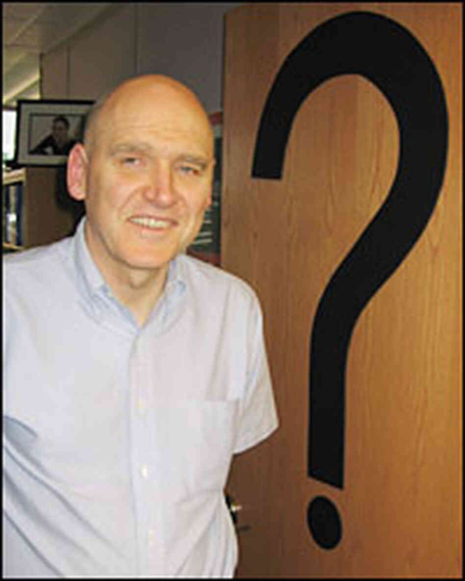 John Sawatsky stands in front of question mark on office door