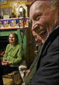 A man laughs as others cavort behind him at the rambling house.