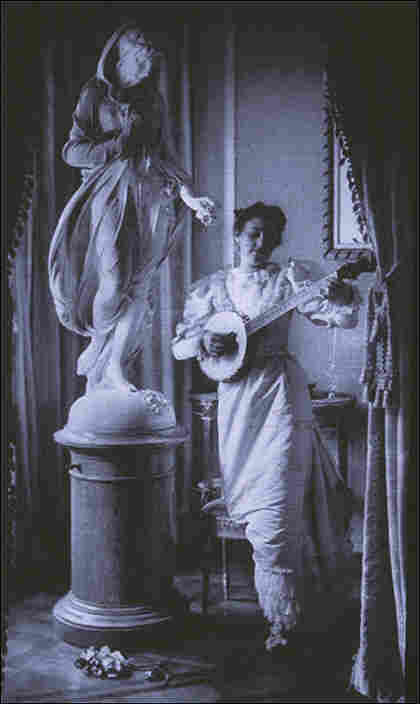'Miss Apperson' playing banjo beside statue of Flora in niche of Sen. George Hearst's residence.