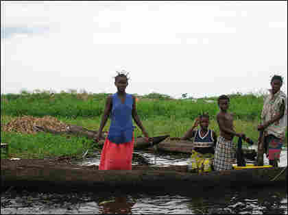 Young people wash clothes from a boat.