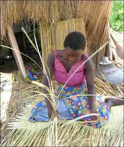 A woman weaves a reed mat.
