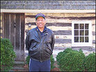 Jim Henson outside the Maryland cabin where his relative, Josiah Henson, lived as a slave.