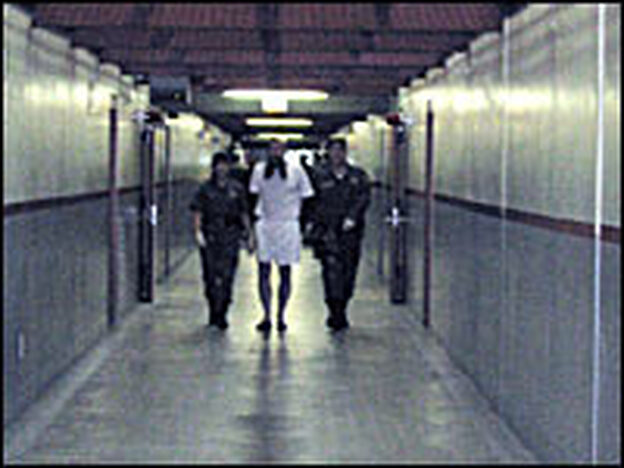 Two prison officers escort an inmate out of his solitary-confinement cell while other officers search his unit for contraband. Almost every prisoner at Pelican Bay wears only underwear.