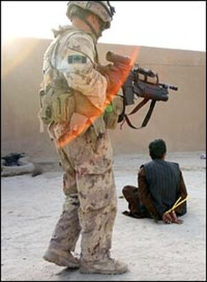 A Canadian soldier guards a suspected Taliban militant.