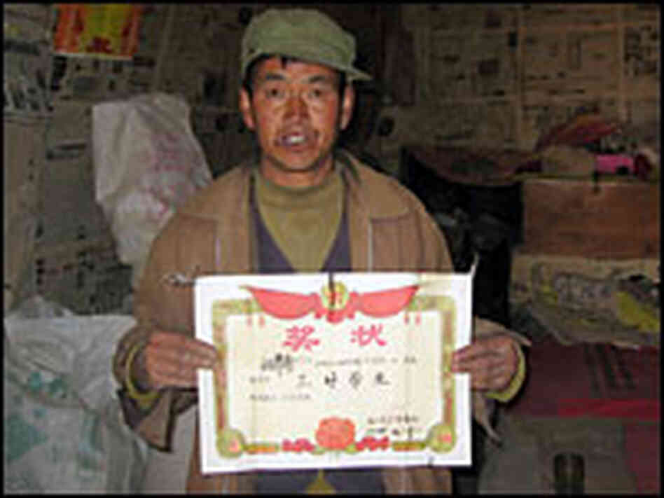 Wei Zijian proudly displays a certificate of academic excellence his son earned