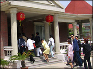 "A tour group enter a ""typical"" Huaxi residence."