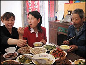 Family members enjoy a 14-dish feast in honor of the return of Wu Dexiu, left, to her home village o
