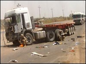 A flatbed truck after attack, as seen in a driver's mirror.