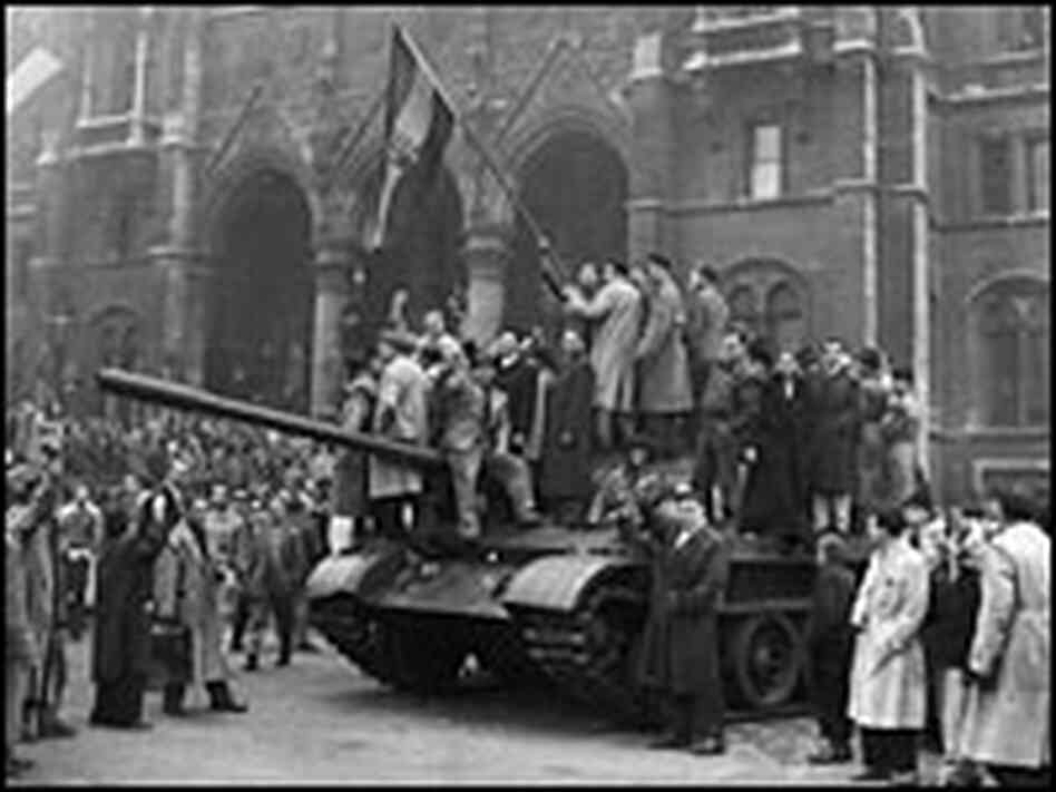 A group of men hold a flag on top of a tank in front of the Parliament building during the Hungarian