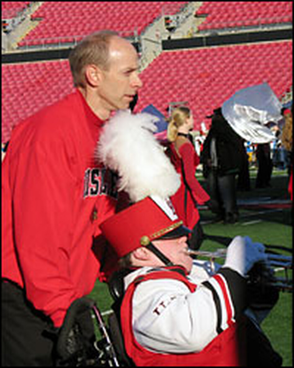 Patrick John Hughes (left) pushes the wheelchair of his son, Patrick Henry Hughes, a member of the University of Louisville marching band.